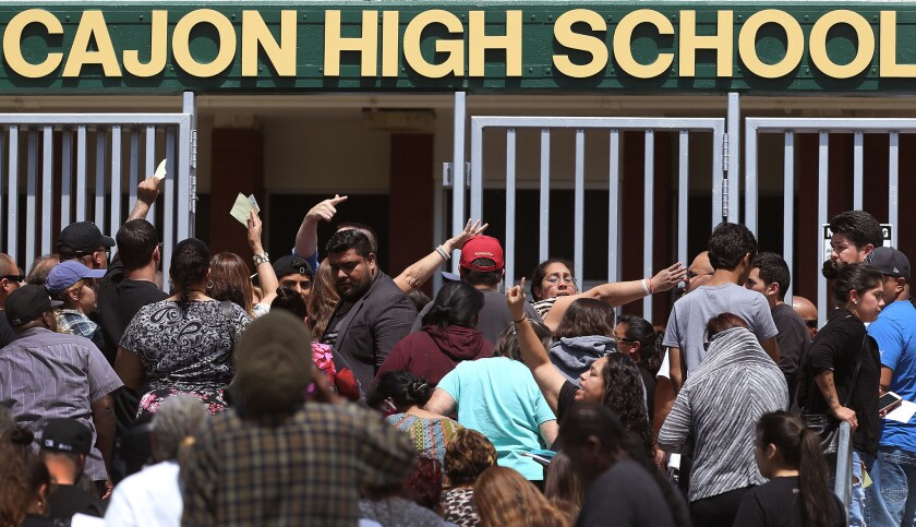 Parents wait to be reunited with their children at Cajon High School after a school shooting at North Park Elementary School.