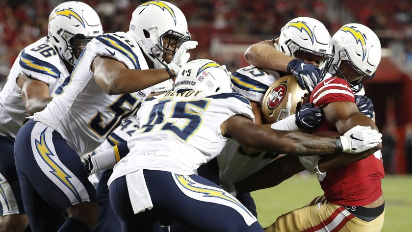 San Francisco 49ers running back Jeremy McNichols, right, is tackled by several Los Angeles Chargers during the second half of an NFL preseason football game in Santa Clara on Thursday.