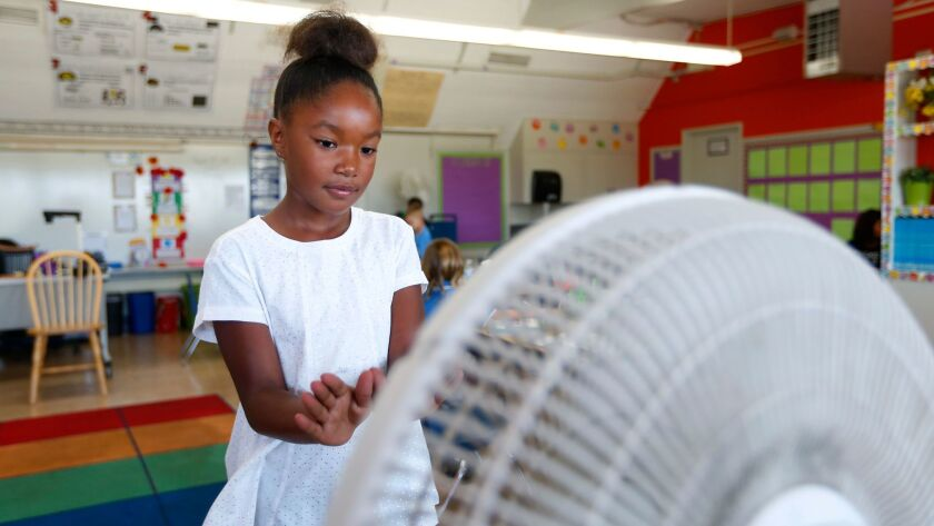 Second grader London Woodard stands in front of a fan at Cadman Elementary School in Clairemont on Tuesday, August 29, 2017.