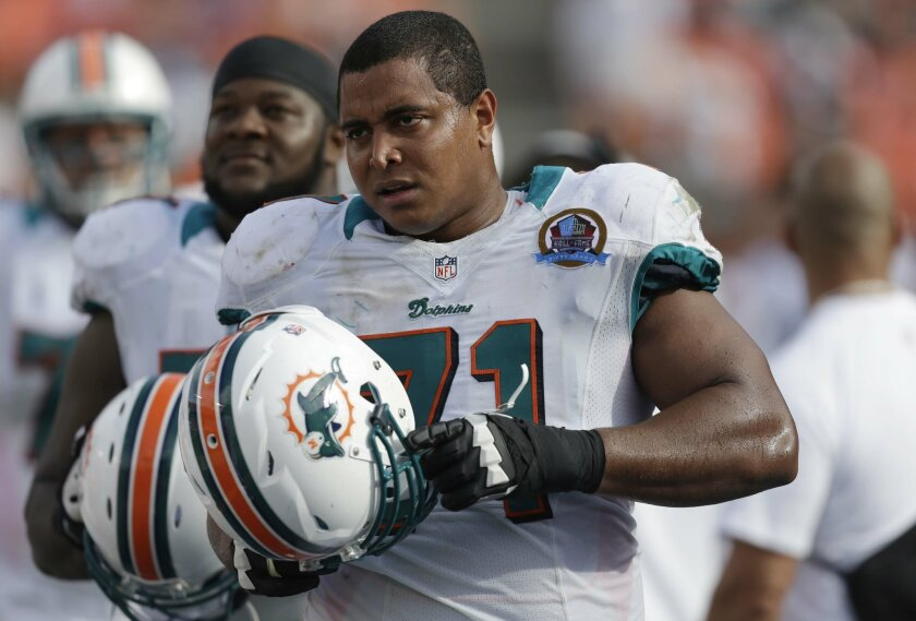 FILE - In this Dec. 16, 2012 file photo, Miami Dolphins tackle Jonathan Martin (71) watches from the sidelines during the second half of an NFL football game against the Jacksonville Jaguars, in Miami. Martin wants to return to the NFL, he said in an interview aired Wednesday where he claimed that