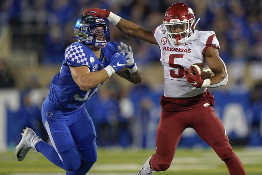 Arkansas running back Rakeem Boyd (5) runs with the ball as he is tackled by Kentucky linebacker Kash Daniel during the first half of an NCAA college football game Saturday, Oct. 12, 2019, in Lexington, Ky. (AP Photo/Bryan Woolston)