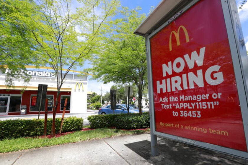 """FILE - In this Monday, July 1, 2019, file photo, a """"Now Hiring"""" sign appears on a bus stop in front of a McDonald's restaurant in Miami. Starting Wednesday, Sept. 25, 2019, McDonald's Corp. will let job seekers start an application by using voice commands on their smartphones with Amazon's Alexa or Google's Assistant. (AP Photo/Wilfredo Lee, File)"""
