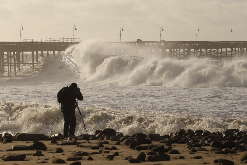 Photographer Dan Dolinh takes photos as the Ventura Pier is pounded by heavy surf Thursday morning.