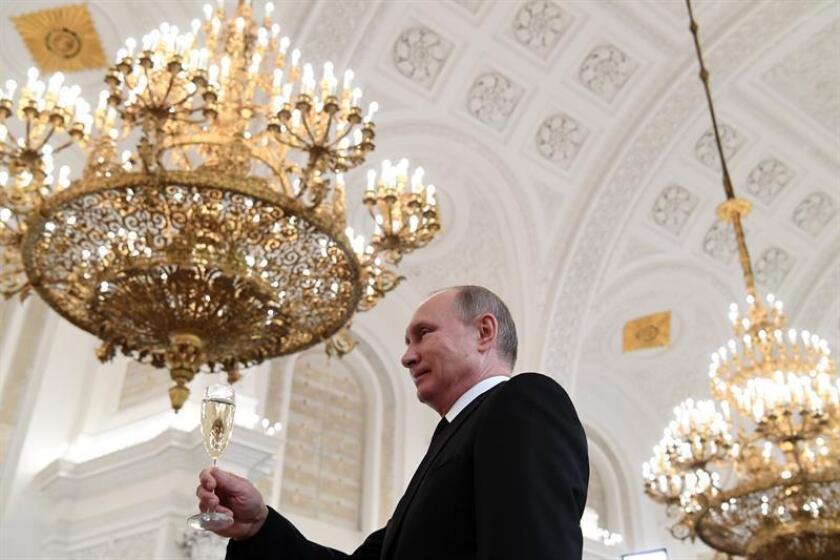 El presidente ruso, Vladímir Putin, hace un brindis durante una ceremonia de condecoración de militares que participaron en las acciones en Siria celebrada en el Kremlin, en Moscú, el pasado 28 de diciembre. EFE