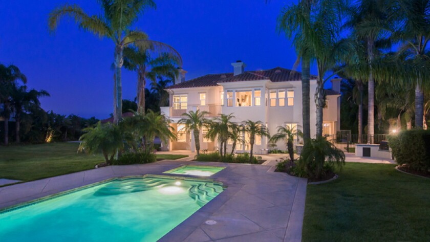 Built in 1997, the two-story home expands to a landscaped front yard and a palm-topped backyard with a gazebo, swimming pool and sand volleyball court.