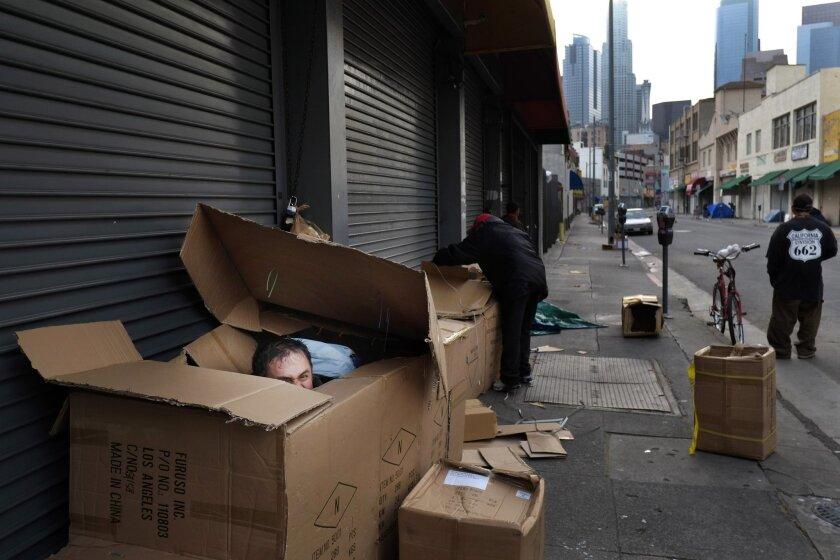 FILE - In this March 29, 2013 file photo, Antonio Garcia, 54, left, who introduced himself as a mathematician, peeks through the opening of his makeshift shelter made of cardboard boxes in the Skid Row area of Los Angeles. Reducing poverty has emerged as the key theme in California after state lawm