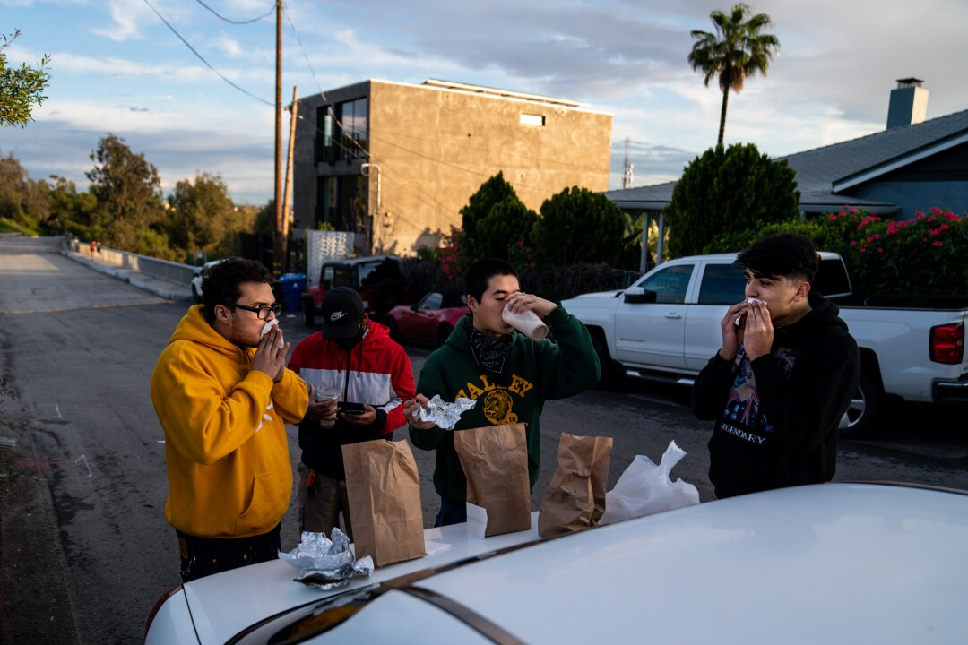 Anthony Calderon, 22, of Echo Park, David Escalante, 19, of Koreatown, Yun Park, 21, of Koreatown, and Antoine Montero, 19, of Los Feliz, eat food from Guisados on the trunk of a car in the Elysian Park neighborhood April 10 in Los Angeles.
