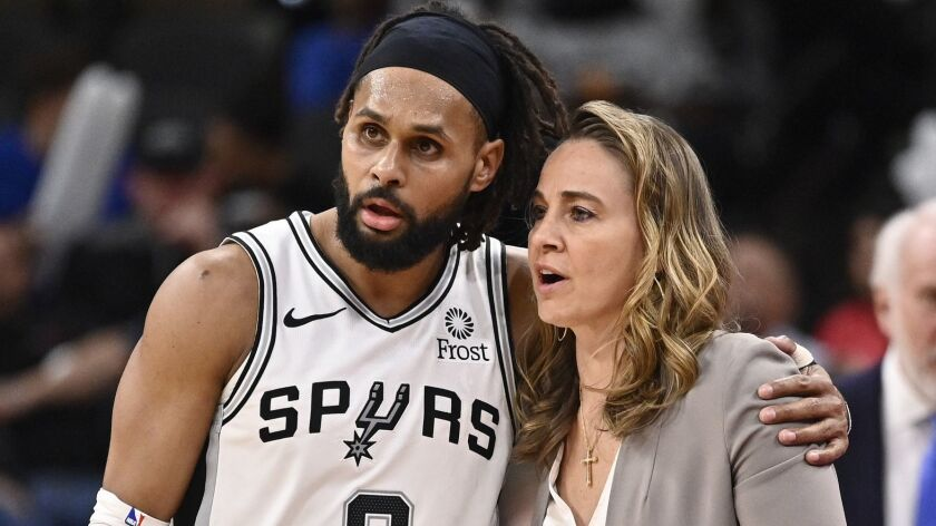 San Antonio Spurs guard Patty Mills (8) talks with Spurs assistant coach Becky Hammon during the sec