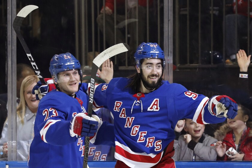 New York Rangers defenseman Adam Fox (23) and center Mika Zibanejad (93) celebrate as they wait for a teammate to join them after Zibanejad scored a goal during the second period of the team's NHL hockey game against the Washington Capitals, Thursday, March 5, 2020, in New York. (AP Photo/Kathy Willens)