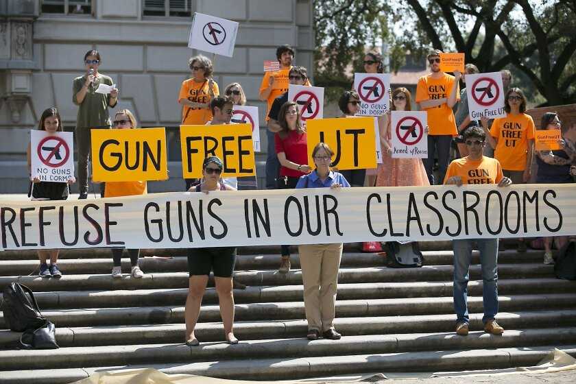 FILE - In this Oct. 1, 2015, file photo, protesters gather on the West Mall of the University of Texas campus to oppose a new state law that expands the rights of concealed handgun license holders to carry their weapons on public college campuses. University of Texas President Greg Fenves has appro