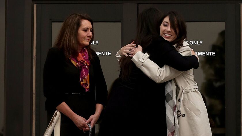 Michelle Hadley, center, gets a hug as she emerges from a Fullerton court where she was exonerated.