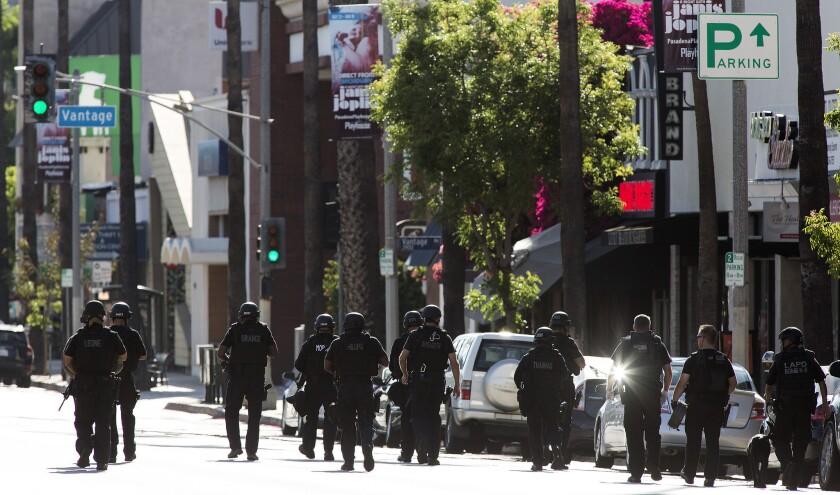LAPD SWAT officers walk toward shooting scene on Ventura Blvd. in Studio City.