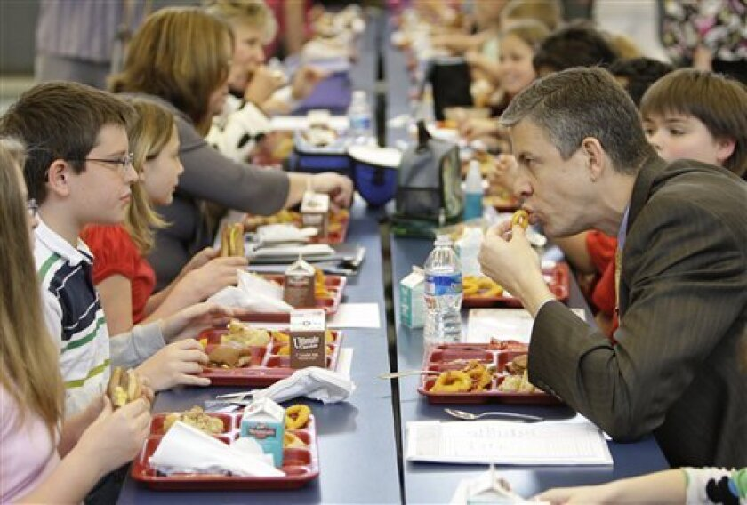 U.S. Secretary of Education Arne Duncan, right, has lunch with students at Eagle School in Martinsburg, W.V. Tuesday, May 5, 2009.(AP Photo/Alex Brandon)