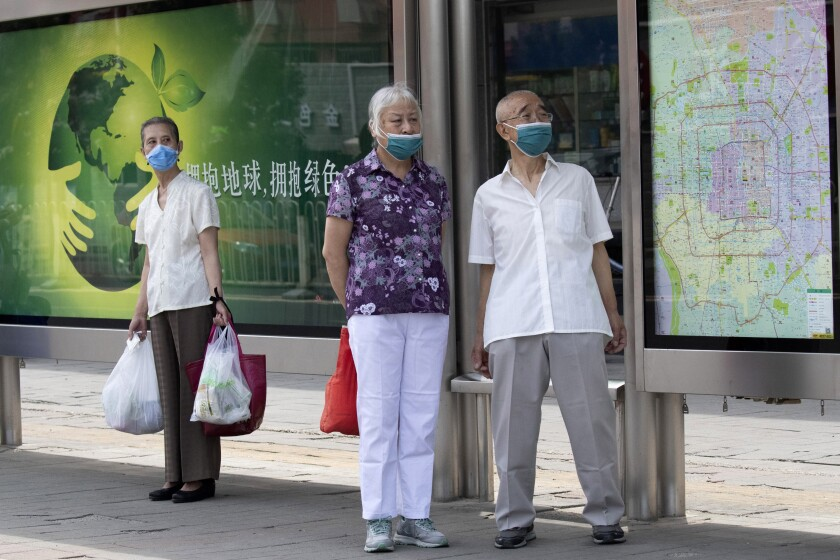 Elderly residents wearing masks to curb the spread of the coronavirus wait at a bus stop with a map of Beijing near a neighborhood under lockdown in Beijing Tuesday, June 16, 2020. Chinese authorities locked down a third neighborhood in Beijing on Tuesday as they rushed to prevent the spread of a new coronavirus outbreak that has infected more than 100 people in a country that appeared to have largely contained the virus. (AP Photo/Ng Han Guan)