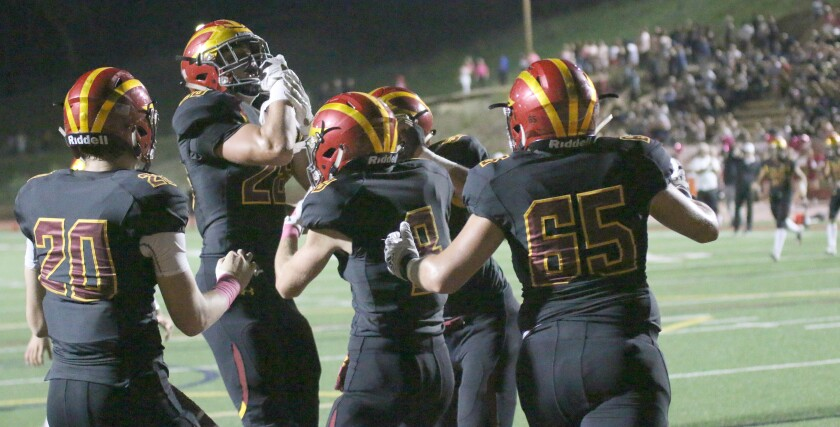 Junior Marco Notarainni (second from left) celebrates with teammates after scoring the game's first touchdown.