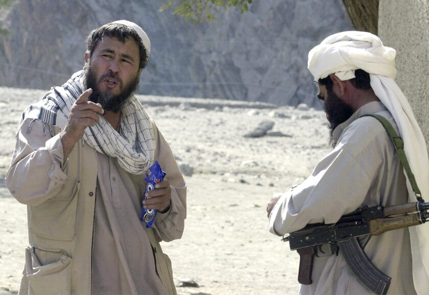 FILE - In this Wednesday, Oct. 24, 2001 file photo, Associated Press correspondent Amir Shah, left, talks with a Taliban fighter in Torkham, Afghanistan. Shah was AP's eyes and ears in Afghanistan after the 9/11 attacks, when all foreigners were ordered to leave. His assignment was dangerous, delicate and often terrifying. (AP Photo/Dimitri Messinis, File)