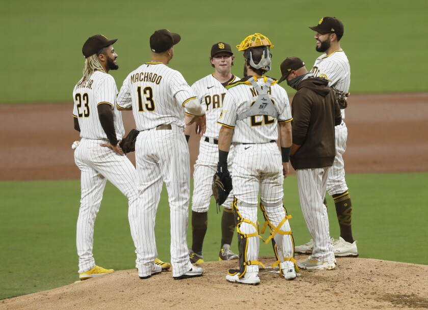Manager Jayce Tingler and members of the Padres infield converse on the mound during a pitching change Saturday night.