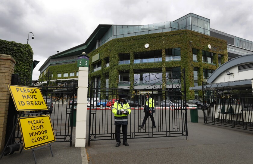 FILE - Security guards are shown at the gate in front of Centre Court at the All England Lawn Tennis Club, after the 2020 tennis championships were canceled due to the coronavirus, in Wimbledon, London, in this Monday, June 29, 2020, file photo. The oldest Grand Slam tennis tournament was the only one that was canceled in 2020 because of the coronavirus pandemic. It was the first time since World War II that Wimbledon was not held. (AP Photo/Kirsty Wigglesworth, File)
