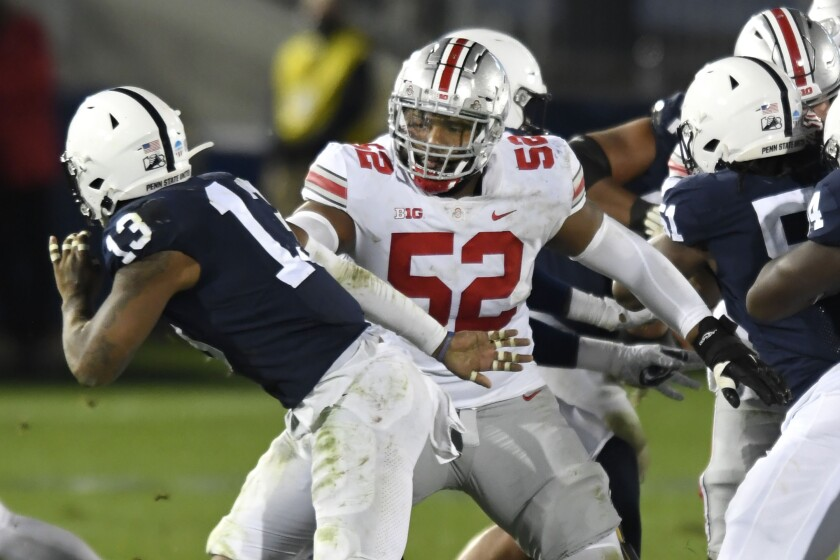 FILE - In this Oct. 31, 2020, file photo, Ohio State offensive lineman Wyatt Davis (52) looks to block Penn State linebacker Ellis Brooks (13) during an NCAA college football game in State College, Pa. Davis is likely to face his biggest challenge of the year when Ohio State meets Alabama in the national championship game on Monday, Jan. 11, 2021. (AP Photo/Barry Reeger, File)