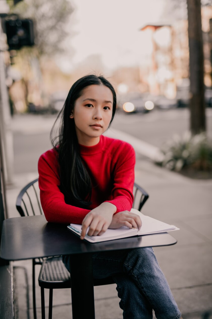 A young woman sits at a cafe table on a sidewalk, hands folded over a notebook.