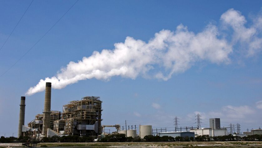 Water vapor is emitted from stacks at the AES power plant in Huntington Beach in 2011. The 1950s-era plant is being replaced by a new plant expected to go live in 2020. AES says it will use 50% less fuel to deliver electrical service, which will lead to lower carbon emissions.