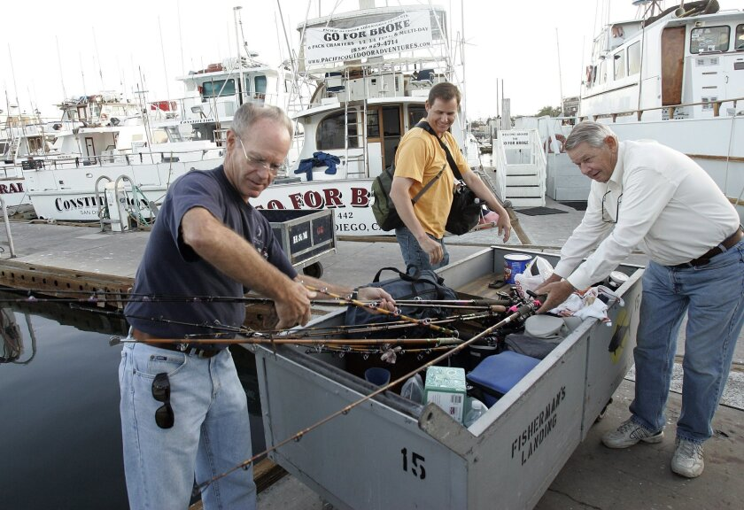 At H&M Landing, anglers Sandy Coger (from left), Jeff Voorheis and Don Voorheis wheeled gear to the dock. (Sean M. Haffey / Union-Tribune)