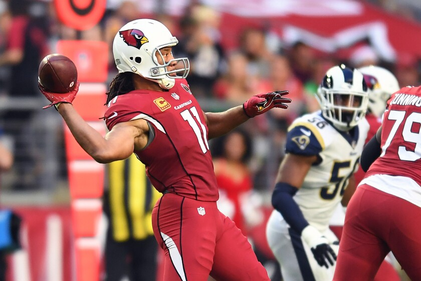 Arizona Cardinals wide receiver Larry Fitzgerald throws a touchdown pass against the Rams in the second quarter at State Farm Stadium on Sunday in Glendale, Ariz.