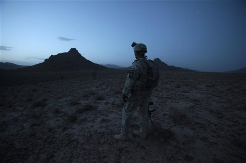 In this May 21, 2010 photo, U.S. Army Staff Sgt. Rande Henderson of Helena, Mont., looks over an area to set up an ambush site in the Shah Wali Kot district of Afghanistan's Kandahar province. Henderson is the platoon sergeant for 2nd Platoon of Charlie Company, 1st Battalion, 17th Infantry Regiment of the 5th Stryker Brigade, 2nd Infantry Division. Twenty-two men in the U.S. Army's 1st Battalion, 17th Infantry Regiment of 800 died in a yearlong Afghan tour ending this summer. Most were killed last year in the Arghandab, a gateway to the southern city of Kandahar. About 70 were injured, all but two in bomb blasts. (AP Photo/Julie Jacobson)