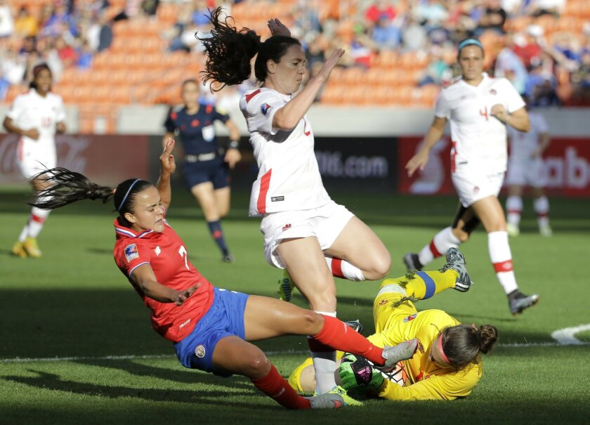 Canada goalkeeper Erin McLeod, right, grabs the ball as Allysha Chapman (2) avoids her as Costa Rica's Melissa Herrera (7) slides during the first half of a  CONCACAF Olympic women's soccer qualifying championship semifinal Friday, Feb. 19, 2016, in Houston. (AP Photo/David J. Phillip)