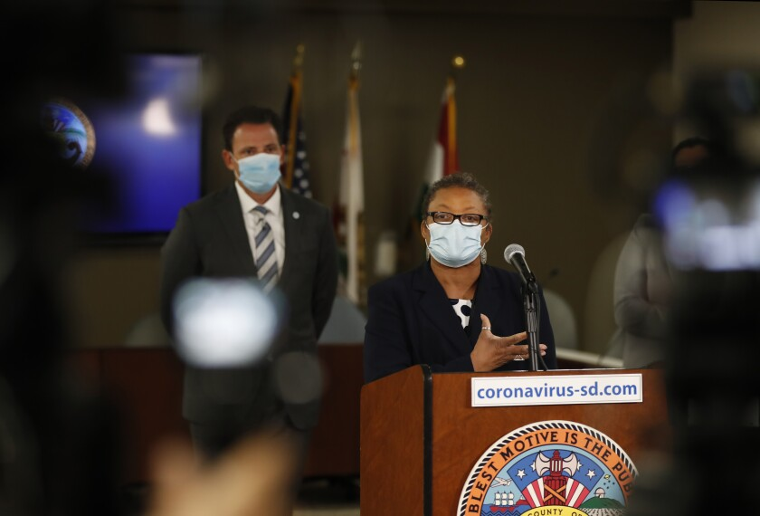 Dr. Wilma Wooten speaks as San Diego County Supervisor Nathan Fletcher looks on at a news conference on Monday.