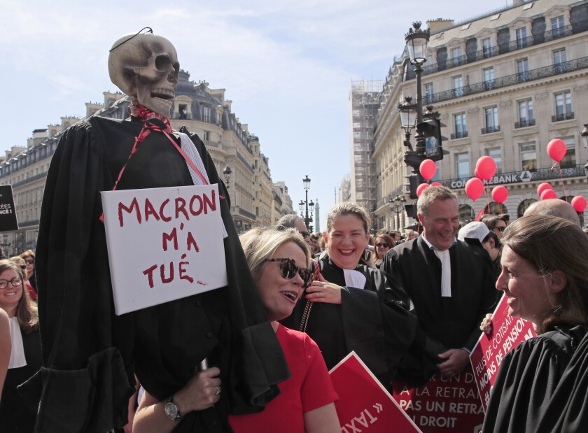 """FILE - In this Sept.16, 2019 file photo, a lawyer hold a effigy with a scull representing a dead lawyer marches during a protest against the planned pension reforms in Paris. French President Emmanuel Macron may face the greatest challenge of his term with the planned overhaul of the retirement system, which has already prompted strikes and protests. Placard reads, Macron is killing me"""". (AP Photo/Michel Euler)"""
