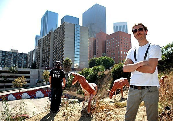 Street artist Calder Greenwood, right, and Wild Life, an anonymous artist who works with Greenwood, stand among their most recent installation of papier-mache creations: three deer perched above a parking lot on Hill Street in downtown Los Angeles.