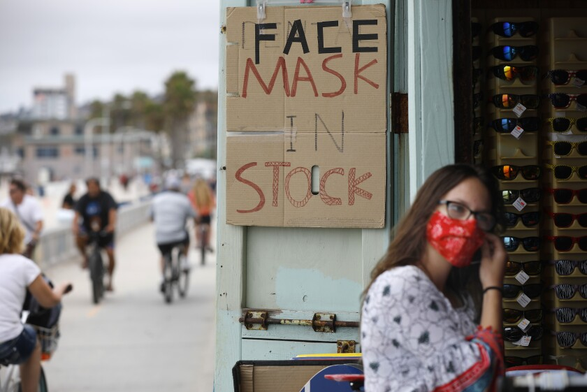 Alexa Gray wears a mask as she enters a souvenir shop along the Pacific Beach boardwalk that was selling them.