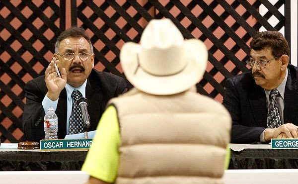 Mayor Oscar Hernandez tells Bell resident Jose Orozco his time is up during a meeting filled with residents upset over the high salaries paid to city administrators. The overwhelming number of public speakers called for their resignations.