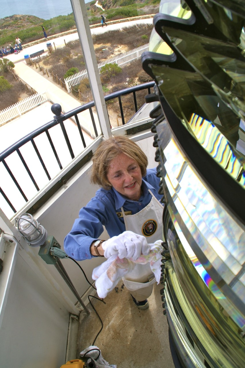 Karen Scanlon wipes the lens of the Old Point Loma Lighthouse, which she cleans as a team with her twin sister, Kim Fahlen.