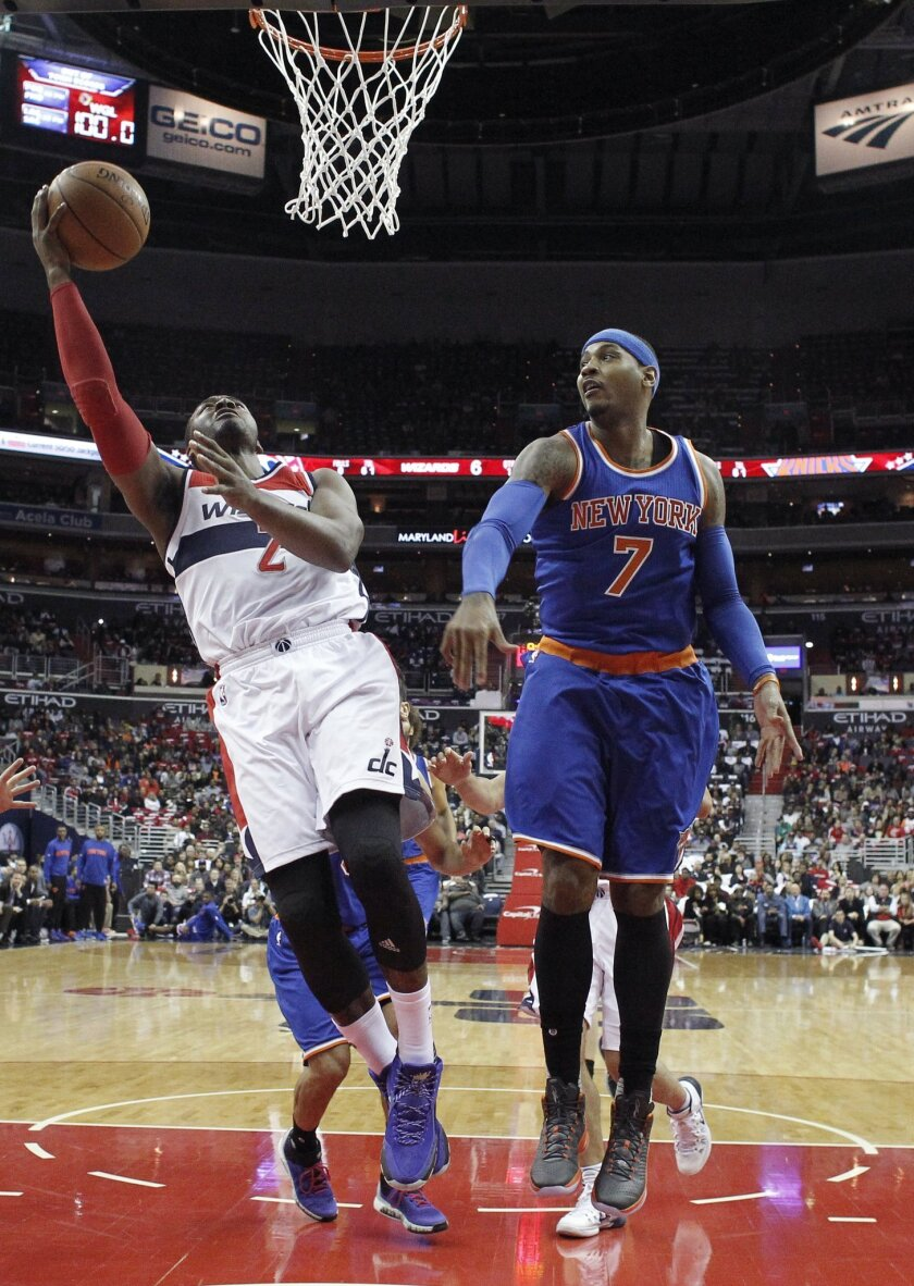 Washington Wizards guard John Wall (2) shoots in front of New York Knicks forward Carmelo Anthony (7) in the first half of an NBA basketball game, Saturday, Oct. 31, 2015, in Washington. (AP Photo/Alex Brandon)