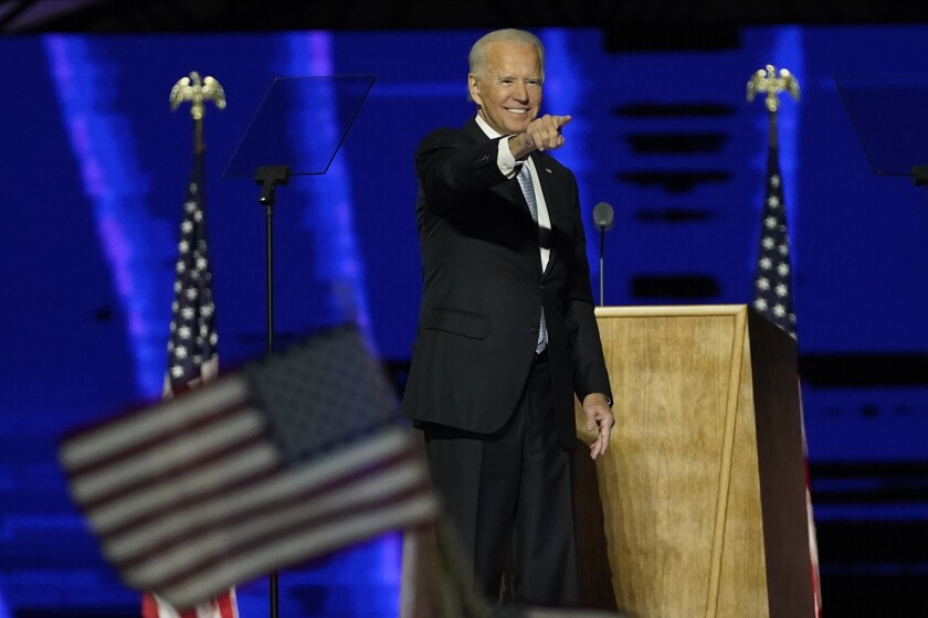 Democratic presidential candidate former Vice President Joe Biden removes his face mask as he arrives to speak Friday.