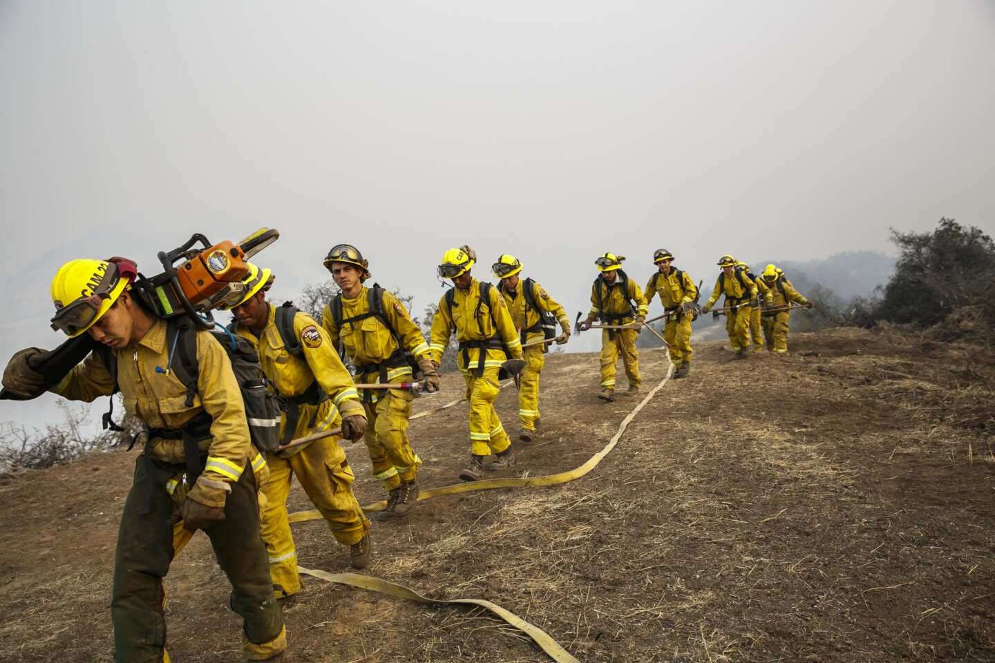 Firefighters return during a shift change after working overnight, conducting burnout operations to corral the Sherpa fire in El Capitan Canyon in Goleta on June 18, 2016.