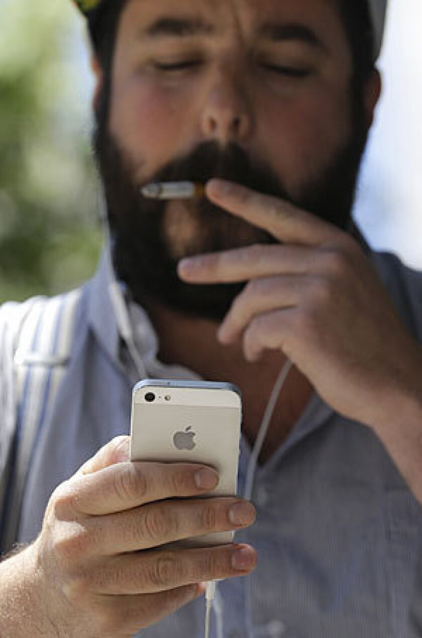 Brian Bocchino uses his iPhone at Union Square in San Francisco on Wednesday. San Francisco's district attorney and New York's attorney general say they will meet with major cellphone manufacturers to push the industry to do more to protect consumers from violent crimes connected to cellphone thefts.