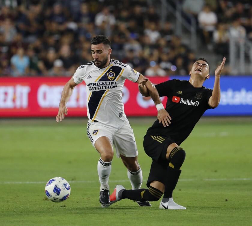 LOS ANGELES, CALIF. -- THURSDAY, JULY 26, 2018: LA Galaxy midfielder Romain Alessandrini, left, batt