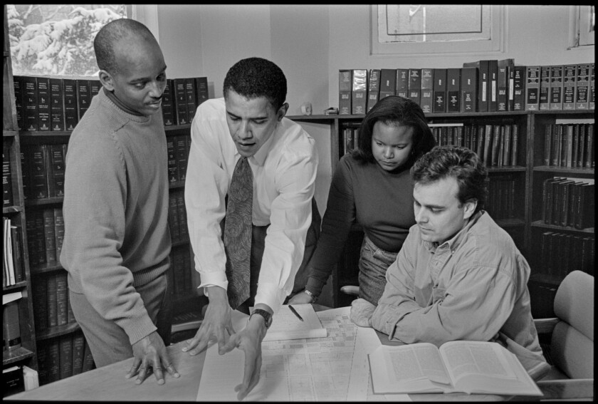 Barack Obama leans over a table in a library, flanked by three people, in a black-and-white image from a 1995 campaign.