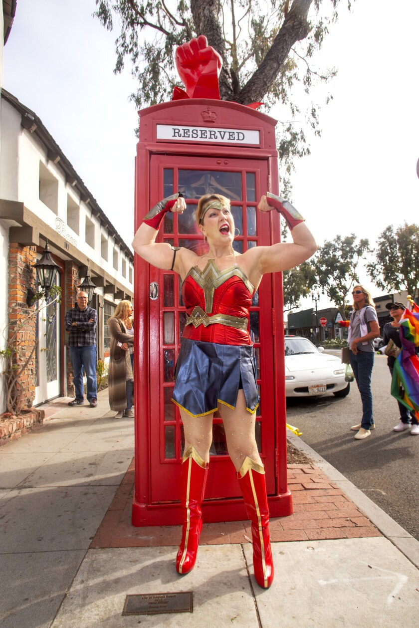 """Heidi Miller, dressed as Wonder Woman, in front of Robert Holton's """"Superhero Changing Station"""""""