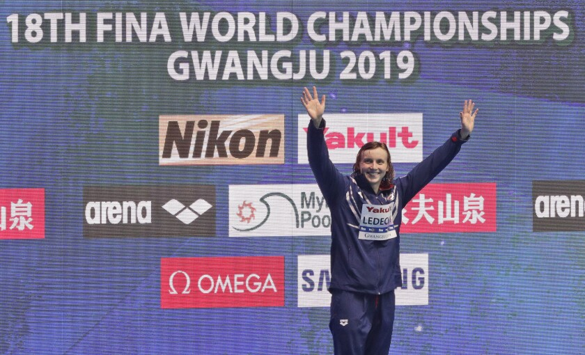 File-This July 27, 2019, file photo shows gold medalist Katie Ledecky of the United States waving on the podium following the women's 800m freestyle final at the World Swimming Championships in Gwangju, South Korea. Like everyone else, Ledecky was forced to shelve her plans when the coronavirus pandemic took hold. Instead of looking far into the future, the five-time Olympic champion swimmer switched to a more immediate mindset. Forget that the four-year cycle leading to the 2024 Paris Olympics is already underway. Ledecky is still working toward making a big splash at this summer's delayed Tokyo Games. (AP Photo/Mark Schiefelbein)