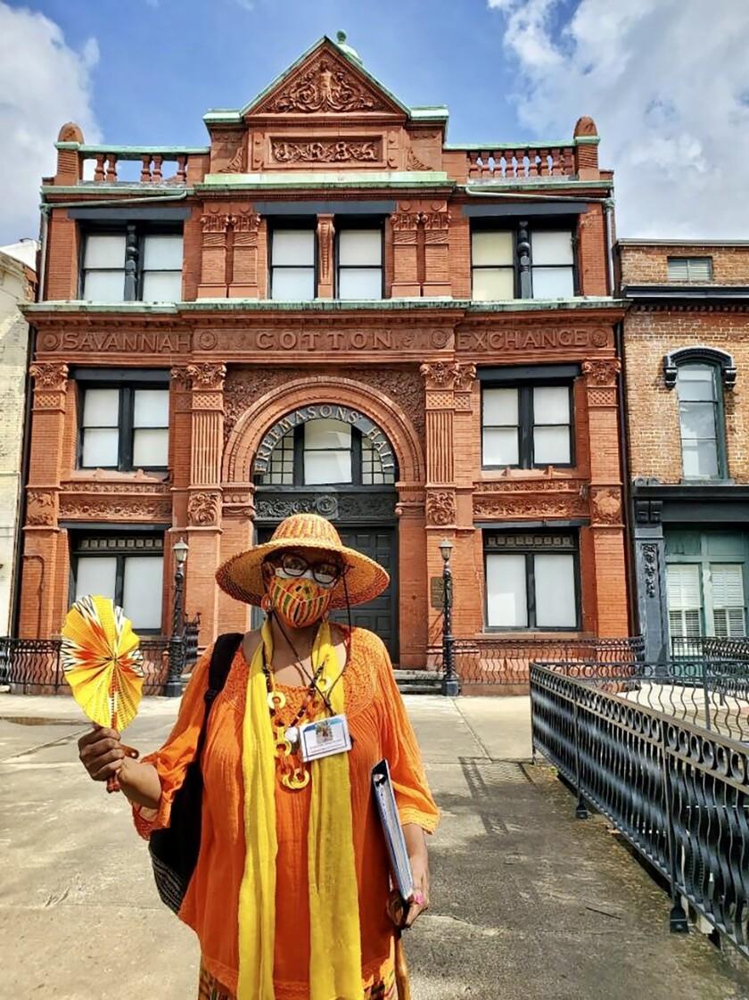 Vaughnette Goode-Walker, founder of Footprints of Savannah Walking Tours, stands in front of the Savannah Cotton Exchange.