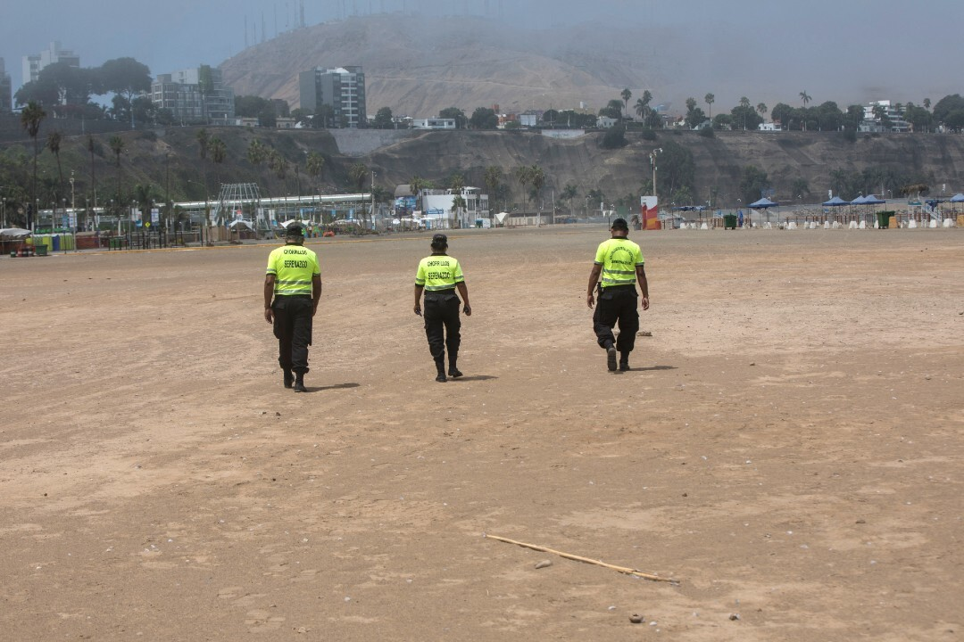 Police walk along the Lima beach to warn off would-be swimmers on March 24.