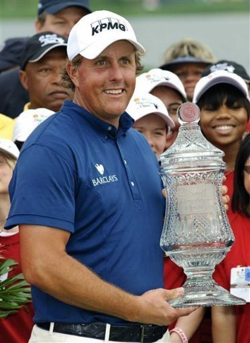 Phil Mickelson holds the championship trophy after winning the Houston Open PGA Tour golf tournament on Sunday, April 3, 2011, in Humble, Texas. Mickelson won the tournament with a 20-under par 268. (AP Photo/Dave Einsel)