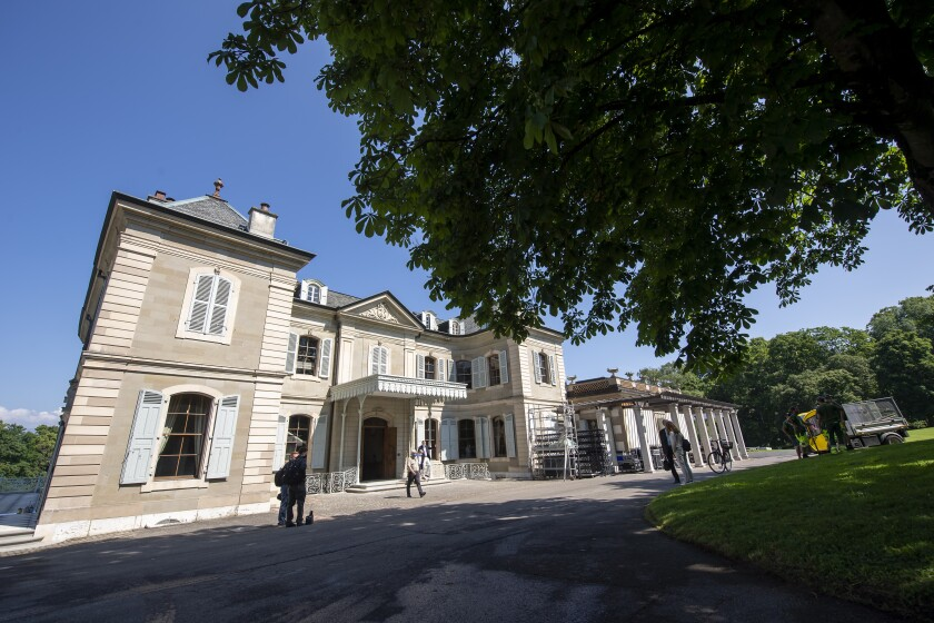 Persons stand in front of the 'Villa la Grange' during a tour for media, in Geneva, Switzerland, Friday, June 11, 2021. The 'Villa La Grange' is the official venue for the meeting between US President Joe Biden and Russian Presidents Vladimir Poutine in Geneva, scheduled for Wednesday, June 16, 2021. (Martial Trezzini/Keystone via AP)