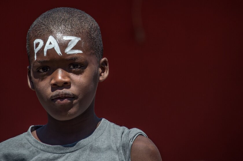 "A boy with the word ""peace"" on his forehead takes part in the march at Rio de Janeiro's Complexo do Alemao favela to protest the police shooting death of a 10-year-old boy."