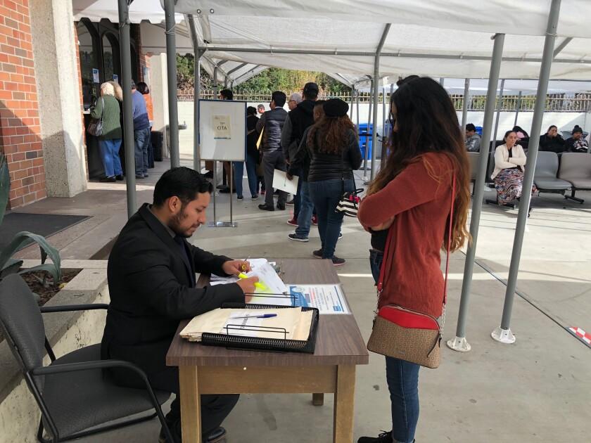 Un funcionario revisa los documentos de una usuaria en la entrada del Consulado General de Guatemala en Los Ángeles.