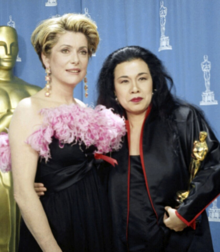 """Actress Catherine Deneuve poses with Eiko Ishioka as she holds her Oscar for best costume design for """"Bram Stoker's Dracula"""" backstage at the 1993 Academy Awards in Los Angeles."""